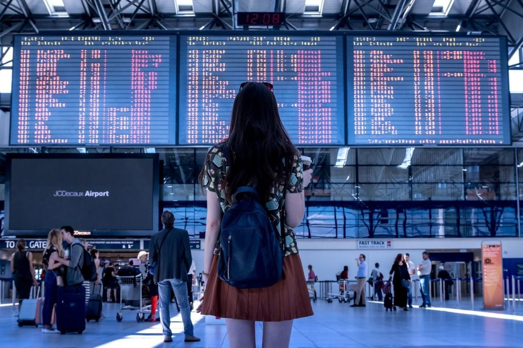 Girl standing in front of an airport flight schedule