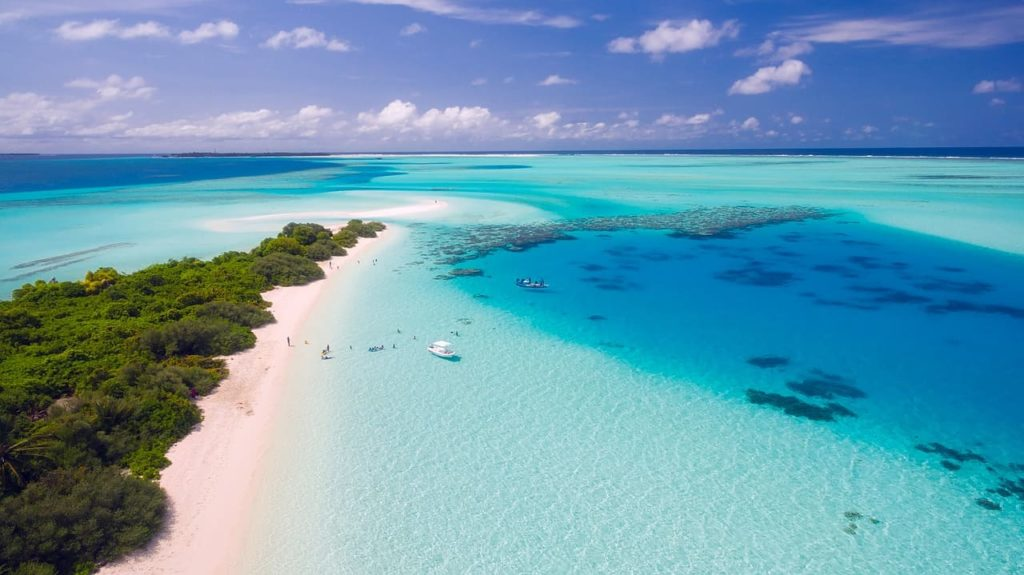 A sandy peninsula in the maldives surrounded by crystal blue water